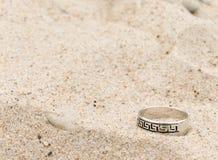 De zilveren ring legt op zand Royalty-vrije Stock Foto's