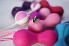 De zilveren ring met bdsmsymbool Triskel ligt op een reeks vaginale ballen van het geslachtsspeelgoed op een witte achtergrond in royalty-vrije stock fotografie