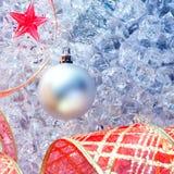De zilveren snuisterij van Kerstmis en rood lint op ijs Royalty-vrije Stock Afbeeldingen