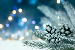 De zilveren tak van de Kerstmisboom met denneappels op vage backgrou Stock Afbeelding
