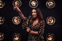 De zingende vrouw die met retro microfoon met richten dient Di in royalty-vrije stock foto's