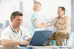 De zitting die van de arts bij bureau, verpleegster patiënt onderzoekt.