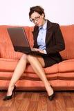 De zitting die van de vrouw aan overlappings hoogste computer werkt Stock Foto