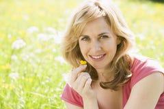 De zitting die van de vrouw in openlucht bloem het glimlachen houdt Stock Foto