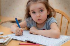 De zitting die van het babymeisje bij de lijst schrijven Stock Foto
