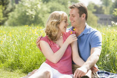 De zitting die van het paar in openlucht bloem het glimlachen houdt Stock Foto