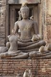 De zitting van de aapfamilie het spelen op het oude beschadigde standbeeld van Boedha, het Spontane dierlijke wild Stock Fotografie