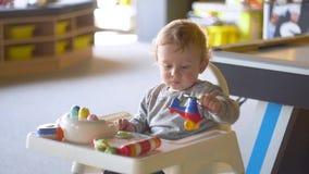 De zitting van de babyjongen als voorzitter en het spelen met speelgoed stock videobeelden