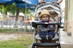De zitting van de babyjongen in babywandelwagen royalty-vrije stock afbeelding