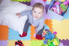 De zitting van de babyjongen over de mat van het raadselspel De mijlpalen van de zittingsbaby royalty-vrije stock afbeeldingen