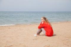 De zitting van de blondevrouw alleen op een zandig strand stock foto
