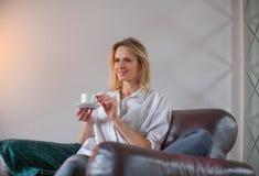 De zitting van de blondevrouw in de leunstoel met koffie royalty-vrije stock afbeelding