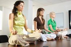 De zitting van Buinesswomen in lotusbloempositie Stock Foto