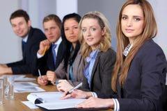 De zitting van Businesspeople bij conferentielijst stock fotografie