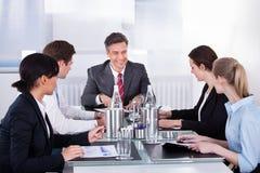 De zitting van Businesspeople bij conferentielijst Stock Foto