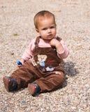 de zitting van de 1 éénjarigebaby op kiezelsteen Stock Foto's