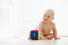 De zitting van de baby binnen met blok het glimlachen stock fotografie