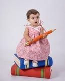 De zitting van de baby op boeken Stock Fotografie