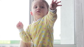 De zitting van de babyjongen bij de venster golvende handen stock footage