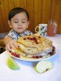 De zitting van de babyjongen bij een lijst met een plaat van pannekoeken Royalty-vrije Stock Foto
