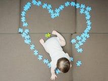 De zitting van de babyjongen in de middendieraadselstukken als vorm van hart op bank thuis woonkamer worden gevouwen stock fotografie
