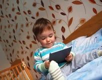 De zitting van de babyjongen op het bed die tablet bekijken Stock Foto