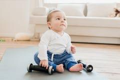 De zitting van de babyjongen op yogamat met domoren Stock Foto's