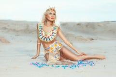 De zitting van de blondevrouw op het zand Royalty-vrije Stock Afbeeldingen