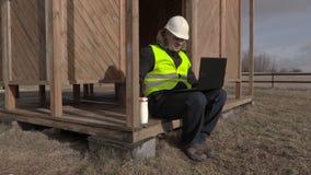 De zitting van de bouwingenieur, het drinken koffie en het gebruiken van laptop stock videobeelden