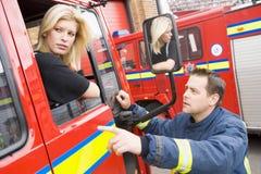De zitting van de brandbestrijder in cabine het spreken Stock Afbeeldingen