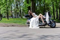 De zitting van de bruid op een motorfiets stock afbeeldingen