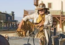 De zitting van de cowboy op een wagen Stock Foto