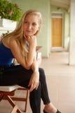De zitting van de dagdromenvrouw op balkon stock afbeeldingen