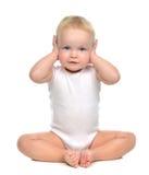 De zitting van de de babypeuter van het zuigelingskind sloot haar handen over oren en Royalty-vrije Stock Afbeelding