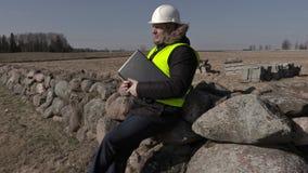 De zitting van de de bouwinspecteur op steenomheining en het gebruiken van laptop stock videobeelden