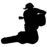 De zitting van de de gitaarspeler van de silhouetmusicus op Stock Afbeeldingen