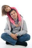 De zitting van de dochter op de schouders van de papa Stock Foto's