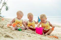 De zitting van de drie babypeuter op een tropisch strand in Thailand en het spelen met zandspeelgoed De gele overhemden Twee jong Royalty-vrije Stock Afbeelding