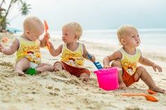 De zitting van de drie babypeuter op een tropisch strand in Thailand en het spelen met zandspeelgoed De gele overhemden Twee jong Stock Afbeeldingen