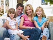 De zitting van de familie bij terras het glimlachen royalty-vrije stock afbeeldingen