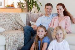De zitting van de familie in de woonkamer Stock Foto