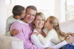 De zitting van de familie in en woonkamer die kust glimlacht Royalty-vrije Stock Afbeeldingen
