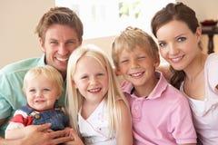 De Zitting van de familie op Bank thuis samen royalty-vrije stock afbeeldingen