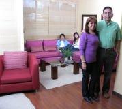 De zitting van de familie op een bank Stock Foto