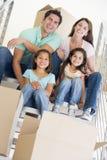 De zitting van de familie op trap met dozen in nieuw huis Stock Foto