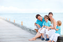 De zitting van de familie in openlucht bij kust Stock Afbeeldingen