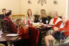 De zitting van de familie rond de dinerlijst Stock Foto's