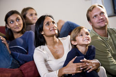 De zitting van de familie samen op bank die op TV let stock foto's