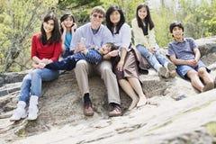 De zitting van de familie samen op rotsachtige richel stock afbeeldingen