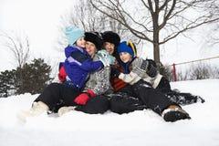 De zitting van de familie in sneeuw. royalty-vrije stock fotografie